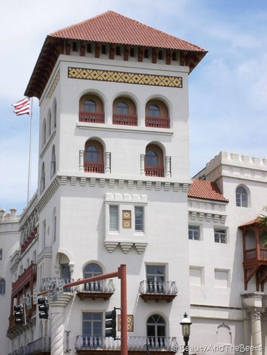 a stark white building with a tower and a spanish tile roof with a balcony and an American flag flying in the background against a blue sky