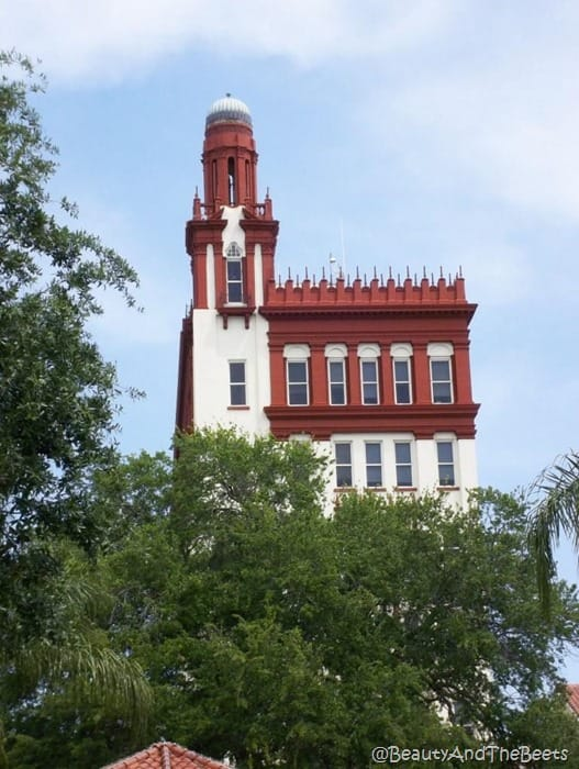 a view of a brown and white spanish style building peering out over the trees against a bright blue sky