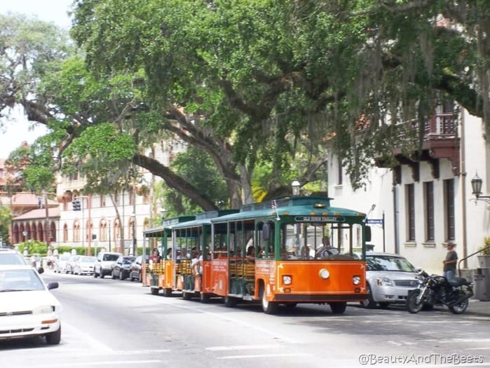 an orange trolley with a green roof on a street in St augustine with spanish architecture in the background