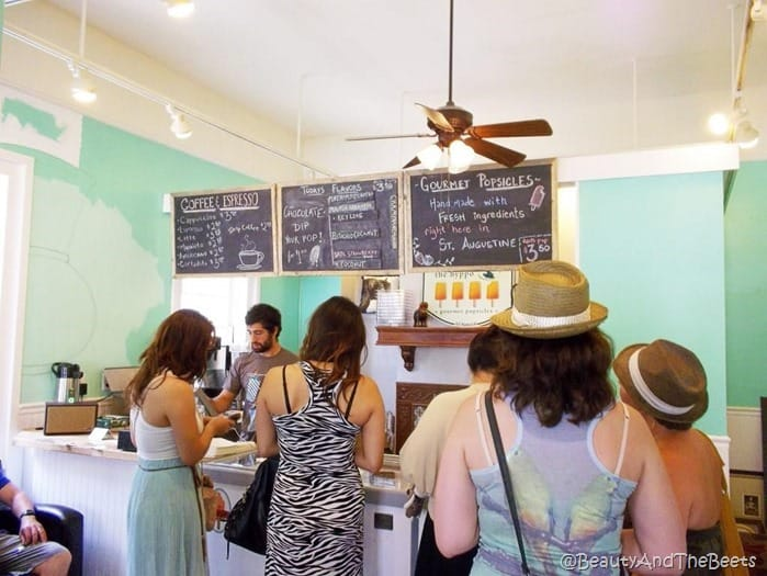 a line of customers in the Hyppo with the popsicle menu overhead and light green walls