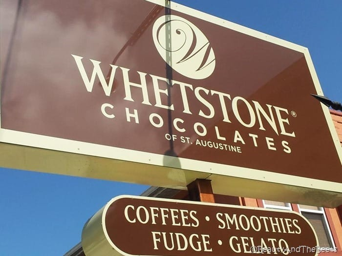 a large chocolate brown and cream colored sign reading Whetstone Chocolates of St Augustine against a bright blue sky