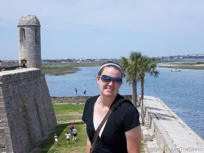 the author on the top of the spanish fort with a lookout tower to the left and the sea and palm trees in the background
