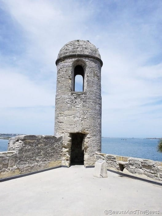a stone tower with a lookout with the sea in the background and a blue sky