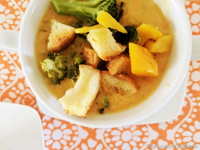 Bread croutons, butternut squash and roasted broccoli in a creamy carrot soup in a white soup cup on an orange placemat