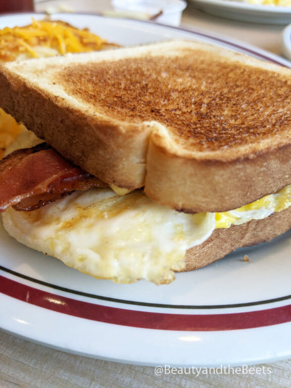 a large piece of toasted bread with bacon, egg, and cheese on a white plate with a maroon and green striped border