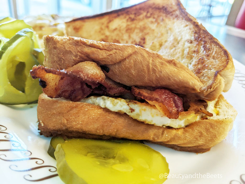 Thick bread sandwich with bacon, egg, and cheese on a white plate with a large slice of pickle in front of the sandwich and a small pile of pickles behind the sandwich