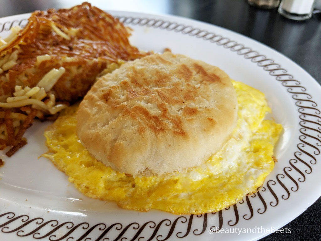 a golden biscuit sandwich with a large overflowing cooked egg next to a pile of crispy hashbrowns on a white plate with a brown squiggly border