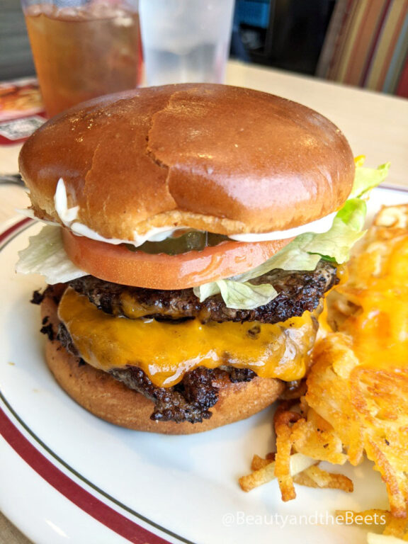 a big double cheeseburger with lettuce, tomato, pickles, and yellow cheese beside some crispy hashbrowns and melted cheese on top on a white plate with a maroon and green striped plate
