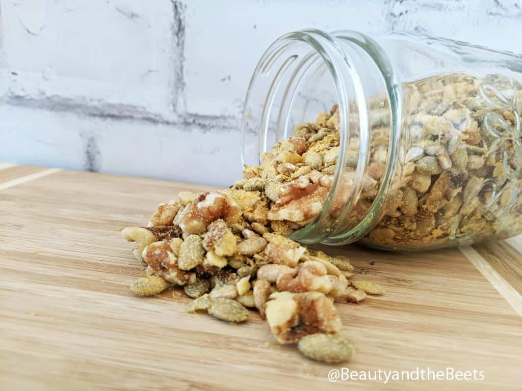 A small mason jar tipped over on its side with walnuts, pepitas, sunflower seeds, and nutritional yeast spilling out of it in front of a white brick background