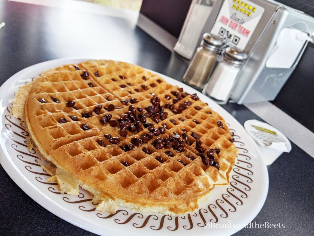 a large golden waffle with a sprinkling of chocolate chips on a white plate with a brown squiggle pattern border in front of a silver napkin dispenser with a pair of glass salt and pepper shakers