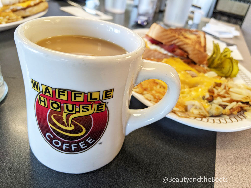 a white coffee cup with the Waffle House lettering logo and the word coffee on a dark gray table with a plate of cheesy hashbrowns in the background