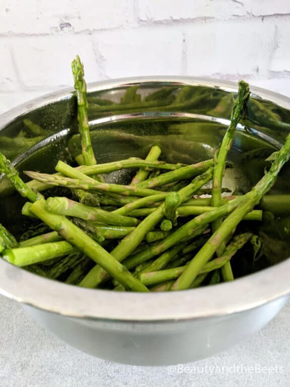 a silver mixing bowl with raw asparagus spears with white brick background