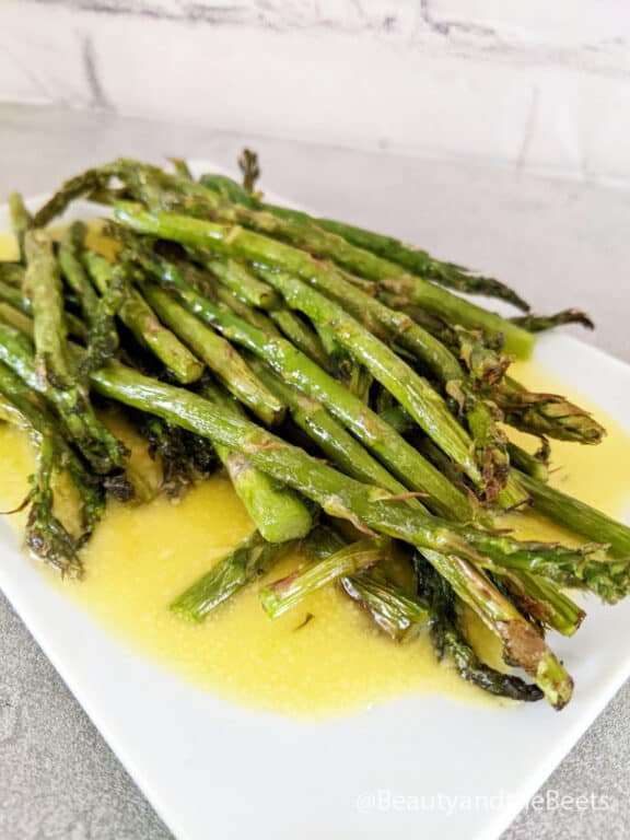 a pile of air fryer asparagus spears on a white plate with hollandaise sauce