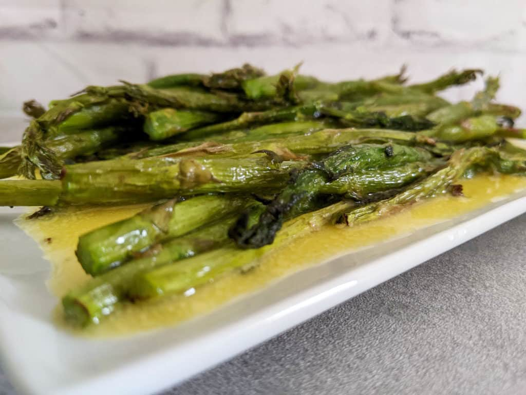air fryer asparagus spears on a long white plate with yellow hollandaise sauce drizzled over the top