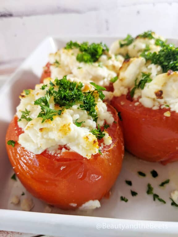 A white plate with four baked tomatoes with goat cheese topped with bright green parsley