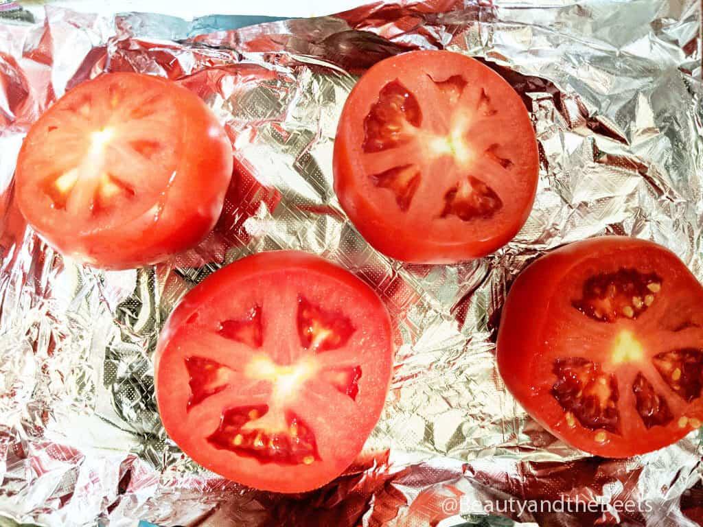an overhead shot of four tomato halves on aluminum foil