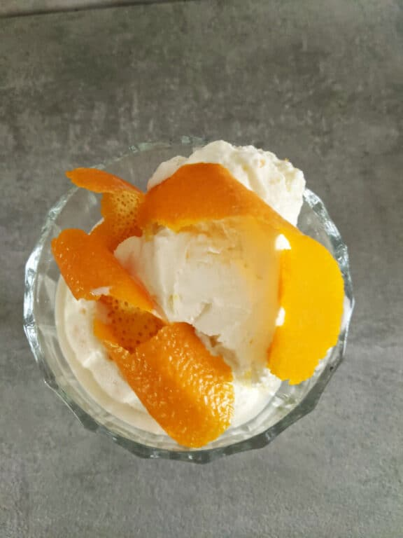 an overhead shot of a glass on a gray stone tabletop with a scoop of vanilla ice cream and bright orange curled peel