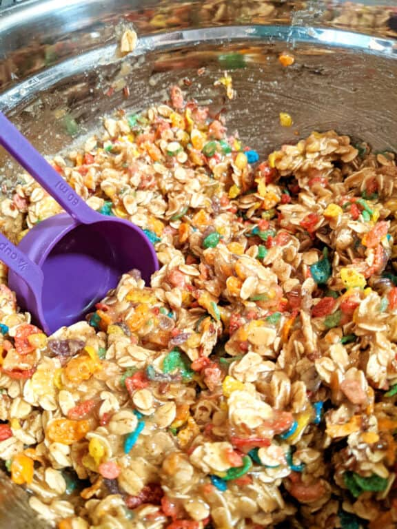 A silver mixing bowl filled with raw Fruity Pebbles cookie dough batter