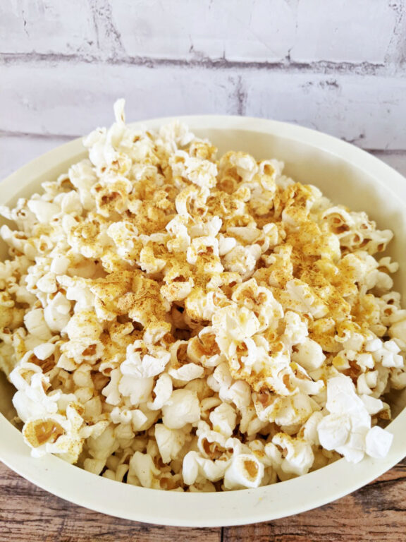 a white bowl filled with popcorn with seasoning and a white brick wall in the background